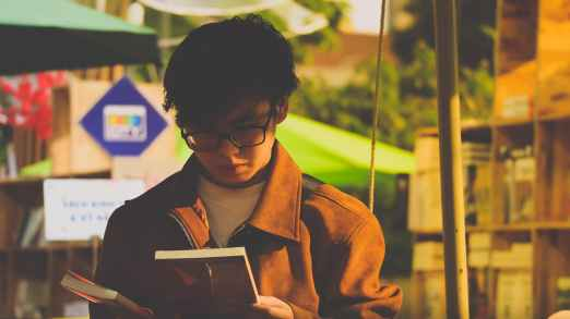 man in brown jacket holding a book